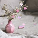 Valentines day decoration with copy space. Dried flowers in pink vase with hearts. Selective focus.  Stock Images