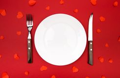 Valentines day dinner with table place decorated with hearts on red background. View from above. - Image