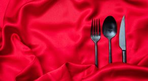 Valentines dinner, Cutlery, fork, spoon and knife on red satin background, copy space, top view royalty free stock images
