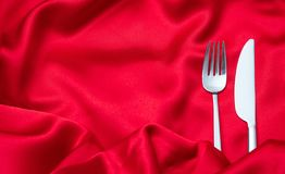 Valentines dinner, Cutlery, fork and knife on red satin background, copy space, top view stock photo