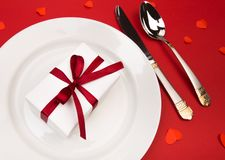 Valentines day dinner with table place setting with gift, decorated with hearts on red background. View from above. - Image royalty free stock photos