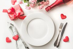 Valentines day dinner with table place setting with red gift, a bottle of champagne, pink roses, hearts with silverware on white. stock photo