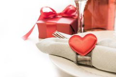 Valentines day dinner with table place setting with red gift, heart with silverware on white background. Close up. Valentine`s ca. Valentines day dinner with Royalty Free Stock Photography