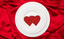 Valentines dinner, Red hearts on white plates, red satin background, top view stock image