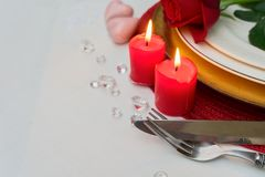 Valentines Day Dinner. Plates with rose flowers, burning candles and cutlery Royalty Free Stock Photos