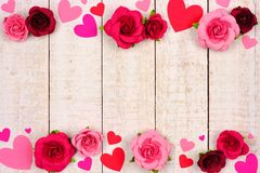 Valentines Day double border of hearts and roses against rustic white wood. Valentines Day double border of red and pink paper hearts and roses against a rustic stock image