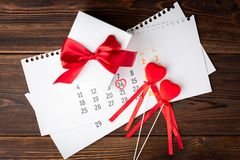 Valentines day. February 14 calendar, gift box and two red hearts on wooden background. royalty free stock images