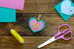 Heart pendant necklace. Felt heart pendant necklace, scissors, thread, felt sheets on a wooden table. Valentines Day jewelry craft Royalty Free Stock Images