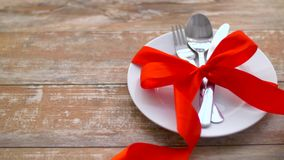 Cutlery tied with red ribbon on plate stock video
