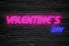 Valentines day. fluorescent Neon tube Sign on dark brick wall. Front view. Can be used for online banner ads or background Stock Photography