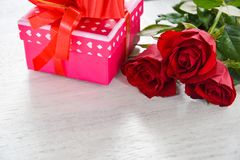 Valentines day gift box flower love concept pink gift box with ribbon bow red roses flower on white wooden royalty free stock images