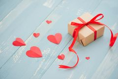 Valentines day. Gift box, paper heart and confetti on blue background top view royalty free stock photo