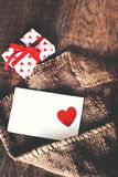 Valentines day  Gift box with red bow ribbon, paper and hearts o. N wooden background Stock Photos