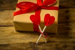Close up of beautiful gift wrapped with red ribbon and heart lollipops on vintage rustic wood background. stock photos