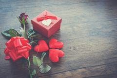 Valentines day gift box red on wood Red Heart Valentines day red rose flower and present box ribbon bow on old wooden royalty free stock photography