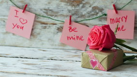 Valentines Day gift with pink rose on wooden background in vintage style. 4k dolly shot left to right.  stock footage