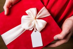 Valentines day gift with gift tag and bow closeup - woman holding in hands present royalty free stock image