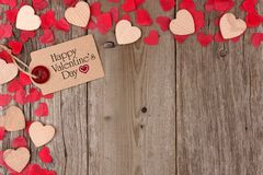 Valentines Day gift tag with heart corner border on wood. Happy Valentines Day gift tag with scattered wooden hearts and confetti corner border on a rustic wood Royalty Free Stock Photo