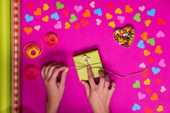 Valentines day gift wrapping with boxes over pink background and colorful paper hearts around Stock Photo