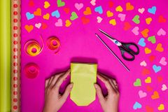 Valentines day gift wrapping with boxes over pink background and colorful paper hearts around Royalty Free Stock Photo