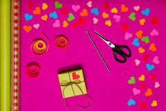 Valentines day gift wrapping with boxes over pink background and colorful paper hearts around Stock Image