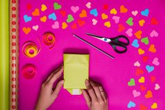 Valentines day gift wrapping with boxes over pink background and colorful paper hearts around Stock Photography