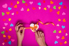 Valentines day gift wrapping with boxes over pink background and colorful paper hearts around Royalty Free Stock Image