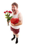 Valentines Day Gifts. Scruffy middle aged man in his underwear with Valentines Day flowers and chocolates for his sweetheart. Isolated on White royalty free stock images
