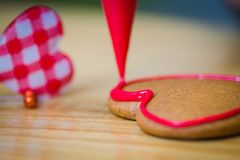 Valentines day gingerbread with dressing. Gingerbread valentines day cake dressing making with heart in the backround Royalty Free Stock Photo