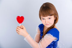 Valentines day girl. Beautiful child girl  holding a lollipop in the shape of a red heart valentines day Stock Image
