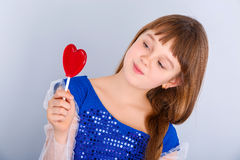 Valentines day girl. Beautiful child girl  holding a lollipop in the shape of a red heart valentines day Royalty Free Stock Photos