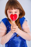 Valentines day girl. Beautiful child girl  holding a lollipop in the shape of a red heart valentines day Royalty Free Stock Photo
