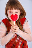 Valentines day girl. Beautiful child girl  holding a lollipop in the shape of a red heart valentines day Royalty Free Stock Image