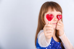 Valentines day girl. Beautiful child girl  holding a lollipop in the shape of a red heart valentines day Stock Photo