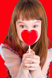 Valentines day girl. Beautiful child girl  holding a lollipop in the shape of a red heart valentines day Royalty Free Stock Images