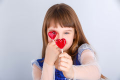 Valentines day girl. Beautiful child girl  holding a lollipop in the shape of a red heart valentines day Stock Images