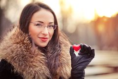 Valentines day girl with gift. Pretty woman holding red heart on Valentines day Royalty Free Stock Images