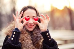 Valentines day girl in love. Pretty woman holding red hearts on Valentines day Stock Image