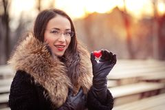 Valentines day girl on the street. Pretty woman holding red heart on Valentines day Royalty Free Stock Photo