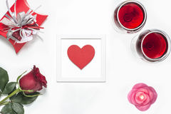 Valentines Day with a glass of red wine, rose, gift, candles and heart view from above Stock Photo