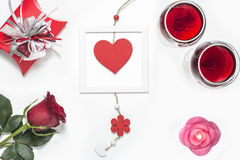 Valentines Day with a glass of red wine, rose, gift, candles and heart view from above Royalty Free Stock Image