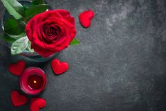Valentines day greeting card concept. Red rose and candle on black background Royalty Free Stock Images