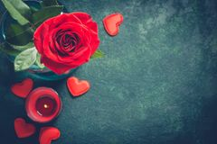 Valentines day greeting card concept. Red rose and candle on  blue background Stock Photos