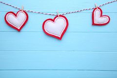 Valentines day greeting card. Handmaded hearts on a rope on blue background royalty free stock images