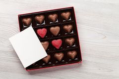 Valentines day greeting card over chocolate box. Valentines day greeting card over heart chocolate box on wooden table. Top view with space for your greetings Royalty Free Stock Images