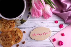 Valentines day greeting card with pink tulips coffe cup cookies and lettering thinking of you. royalty free stock photography