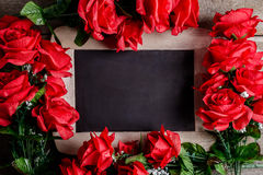 Valentines day greeting card. Red rose flowers and chalkboard on Royalty Free Stock Image