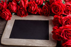 Valentines day greeting card. Red rose flowers and chalkboard on Stock Photo