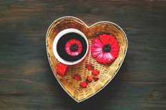 Valentines day greeting postcard. Big red cup of coffee with flo. Wer in heart shaped basket on wooden background. Festive concept. Top view. Closeup, copy space stock photo