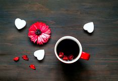 Valentines day greeting postcard. Flower and big red cup of coffee on wooden background. Festive concept. Top view. Closeup, copy space stock images